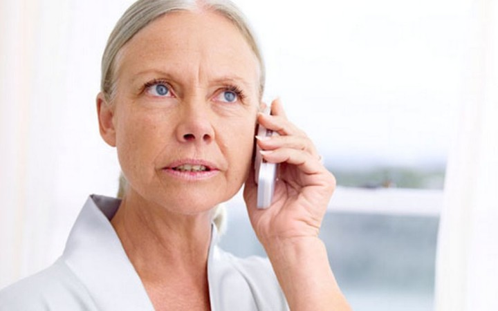Mature woman using telephone, looking upwards